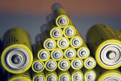 Gelbe Batterien des Doppelten A, die im Spiegel, Stromspeicherkonzept sich reflektieren Stockfoto