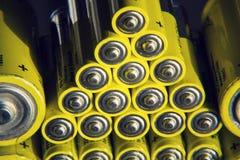 Gelbe Batterien des Doppelten A, die im Spiegel, Stromspeicherkonzept sich reflektieren Stockfotografie