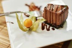 Gelbe Beere auf einer weißen Platte irgendein Schokoladenkäsekuchen und Gabelnahaufnahme Lizenzfreie Stockfotos