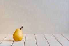 Gelbe Birne auf der weißen Tabelle Stockbilder