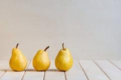 Gelbe Birnen auf der weißen Tabelle Stockfoto