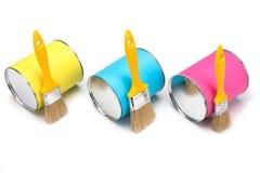 Gelbe, blaue und rosa Dosen der Farbe und des Malerpinsels lokalisiert auf weißem Hintergrund Lizenzfreie Stockbilder