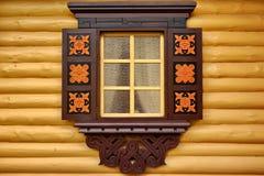 Gelbe Blockhaus-Wand mit einem dekorativen Fenster Lizenzfreies Stockbild