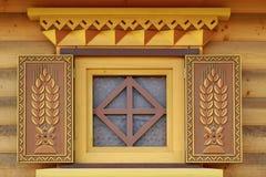 Gelbe Blockhaus-Wand mit einem dekorativen Fenster Lizenzfreies Stockfoto
