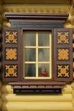 Gelbe Blockhaus-Wand mit einem dekorativen Fenster Stockfoto