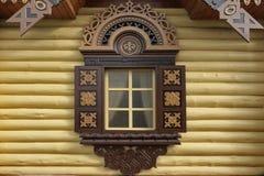 Gelbe Blockhaus-Wand mit einem dekorativen Fenster Stockfotografie
