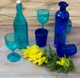 Gelbe Blumen der Mimose dienten auf Holztisch mit blauen Vasen lizenzfreie stockbilder