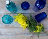 Gelbe Blumen der Mimose dienten auf Holztisch mit blauen Vasen stockfotos