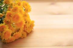 Gelbe Blumen mit hölzernem und kopieren Raum Lizenzfreie Stockfotografie