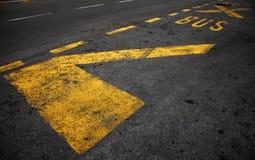 Gelbe Bushaltestellemarkierung auf Asphalt Lizenzfreie Stockfotografie