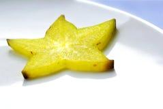 Gelbe Carambolascheibe auf weißer Platte Stockfotos