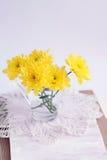 Gelbe Chrysanthemen im Glas auf einer Spitzeserviette Stockfotos