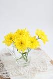 Gelbe Chrysanthemen im Glas auf einer Spitzeserviette Stockbild
