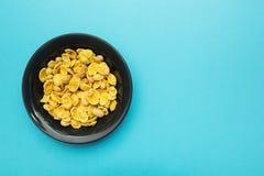 Gelbe Corn Flakes in einem Schwarzblech auf einem blauen Hintergrund Platz für den Text stockbild