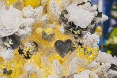 Gelbe Dekorationen auf einem Weihnachtsbaum, Blumenherzen, Schmetterlinge, Schnee Stockfoto