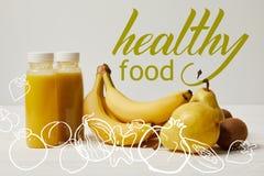 gelbe Detox Smoothies in den Flaschen mit Bananen, Birnen und Kiwis auf weißem Hintergrund, gesunde Lebensmittelaufschrift lizenzfreie stockfotografie