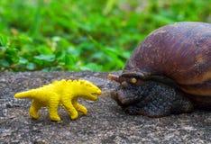 Gelbe Dinosauriermarionette und riesige Schnecke im Garten Lustiges Monstermakrofoto Lizenzfreie Stockbilder