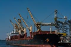 Gelbe dockside Kräne und Schiff am industriellen Hafen in Rostock stockfotografie