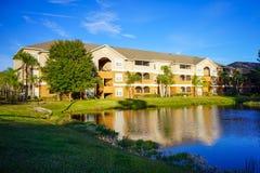 Gelbe Eigentumswohnungen oder Wohnungen und ein kleiner Teich Stockbilder