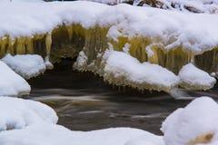 Gelbe Eiszapfen unter Schneedecke Lizenzfreies Stockfoto