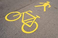 Gelbe Fahrbahnmarkierung, die einen Fahrradweg und -Wanderweg anzeigt Lizenzfreie Stockfotos