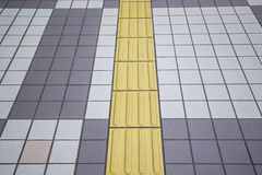 Gelbe farbenblinde Bodenfliesen auf allgemeinem Gehweg Lizenzfreie Stockbilder