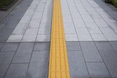 Gelbe farbenblinde Bodenfliesen auf allgemeinem Gehweg Stockfotografie
