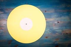 Gelbe Farbvinylaufzeichnung auf blauem hölzernem Hintergrund Stockfotos