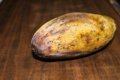 Gelbe faule Mangofrucht lokalisiert auf Holz stockbild