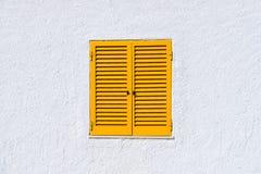 Gelbe Fensterfensterläden und weiße Wand Stockbilder