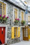 Gelbe Fensterläden auf Steinfassade Stockfoto
