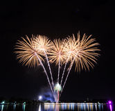 Gelbe Feuerwerke mit Reflexionslichtern auf See Stockbild