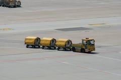 Gelbe Frachtlaufkatzen mit geladenem Gepäck auf dem Rollbahnasphalt stockbilder