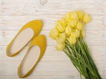 Gelbe Frauen ` s beschuht Ebenen und gelbe Tulpen auf einem hölzernen Licht Stockfotos