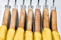 Gelbe Frauen ` s T-Shirts von den verschiedenen Größen, die am hölzernen hange hängen Lizenzfreie Stockbilder