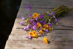 Gelbe Gänseblümchen und Glockenblumen auf den Brettern Lizenzfreie Stockfotografie