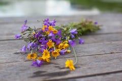 Gelbe Gänseblümchen und Glockenblumen in einem Glas auf den Brettern Stockbilder