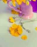 Gelbe Gartenblumen und rosa Schale, Stillleben Stockbild