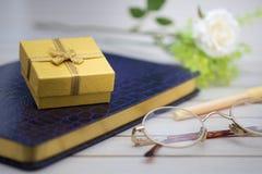Gelbe Geschenkbox gesetzt auf purpurrotes Notizbuch stockbild