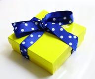 gelbe Geschenkbox und Blau punktiertes Band lokalisiert Lizenzfreie Stockfotografie