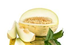 Gelbe geschnittene Melone mit Samen auf weißem Spiegelhintergrundabschluß oben stockfoto