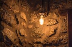 Gelbe Glühlampe, die von der Steinwand hängt lizenzfreie stockbilder