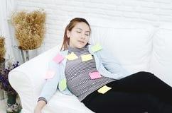 Gelbe, grüne und rosa Papierblätter auf der Frau, die und erschöpft von der Arbeit schläft lizenzfreies stockfoto