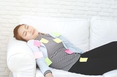 Gelbe, grüne und rosa Papierblätter auf der Frau, die und erschöpft von der Arbeit schläft stockfoto