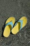 Gelbe Gummisandalen auf sandigem Strand Stockbilder
