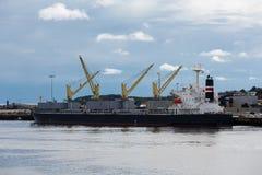 Gelbe Handkurbeln auf Dockside-Frachter Stockfotos