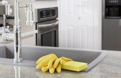 Gelbe Handschuhe und Schwamm in der Küche Stockfotografie