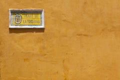 Gelbe Hausmauer mit mit Ziegeln gedecktem Straßenschild Stockfotos