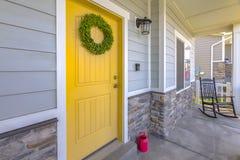 Gelbe Haustür mit Schaukelstuhl Stockfotos