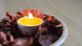 Gelbe helle Kerze in einem Trockenblumengesteck woden Schüssel Weihnachten, Diwali, Feier, Badekurort, Wellness, gesunde Konzepte stock footage